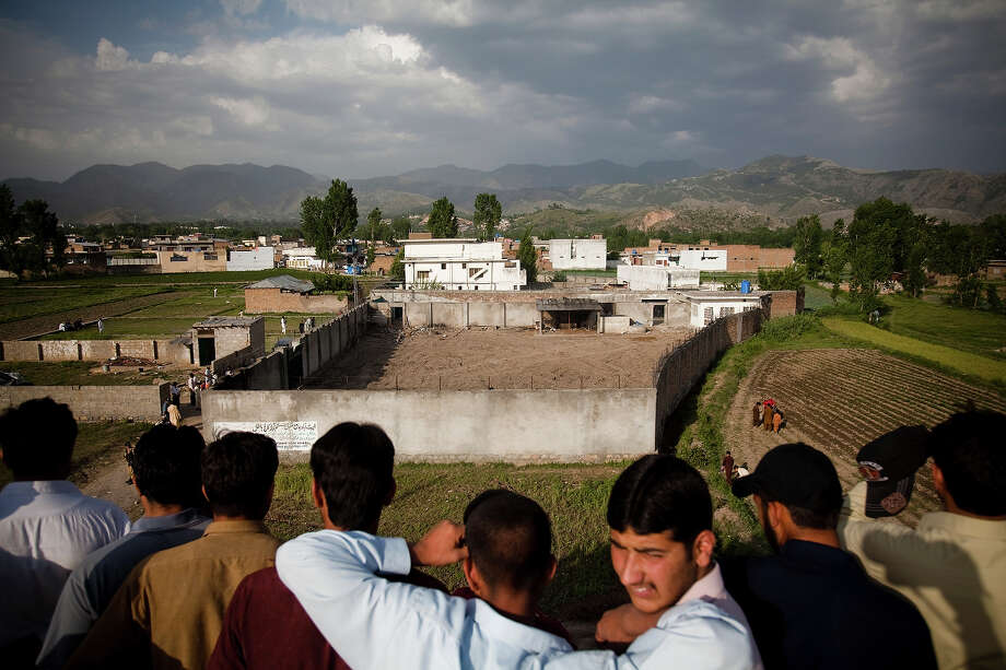 Locals look from atop an adjacent building to the compound where Osama Bin Laden was killed in an operation by US Navy Seals, on May 4, 2011, in Abottabad, Pakistan. Bin Laden was killed during a U.S. military mission on May 2, at the compound. The Obama administration have decided not to release photographs of Bin Laden's body. Photo: Warrick Page, Getty Images / 2011 Warrick Page