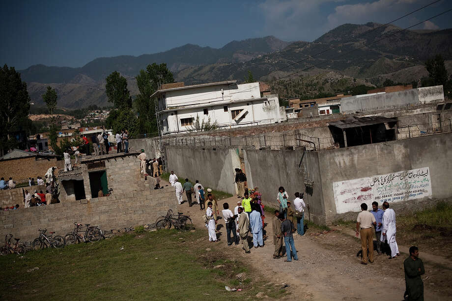 Locals and media gather outside the compound where Osama Bin Laden was reportedly killed in an operation by US Navy Seals, on May 3, 2011, in Abottabad, Pakistan.  Bin Laden was killed during a U.S. military mission on May 2, at the compound. The Obama administration have decided not to release photographs of Bin Laden's body. Photo: Warrick Page, Getty Images / 2011 Warrick Page