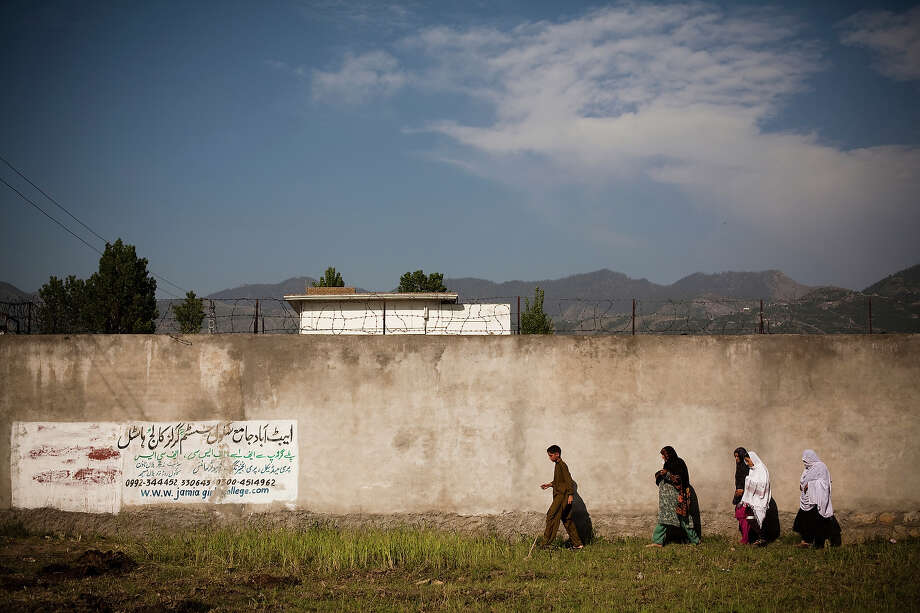 Locals walk past a wall encompassing the perimeter of the compound where Osama Bin Laden was reportedly killed in an operation by US Navy Seals, on May 3, 2011, in Abottabad, Pakistan. Bin Laden was killed during a U.S. military mission on May 2, at the compound. The Obama administration have decided not to release photographs of Bin Laden's body. Photo: Warrick Page, Getty Images / 2011 Warrick Page