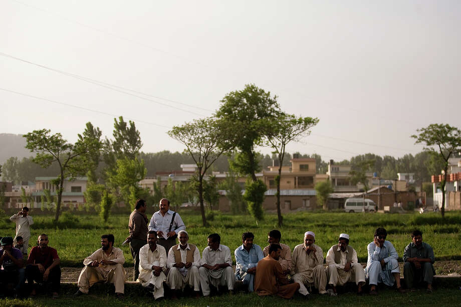 Locals gather outside the compound where Osama Bin Laden was killed in an operation by US Navy Seals, on May 4, 2011, in Abottabad, Pakistan.  Bin Laden was killed during a U.S. military mission on May 2, at the compound. The Obama administration have decided not to release photographs of Bin Laden's body. Photo: Warrick Page, Getty Images / 2011 Warrick Page