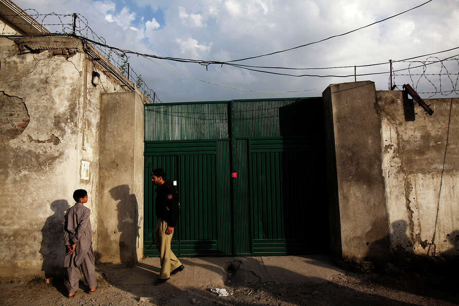 A Pakistani policeman talks with a young boy at the entrance to the compound where Osama Bin Laden w