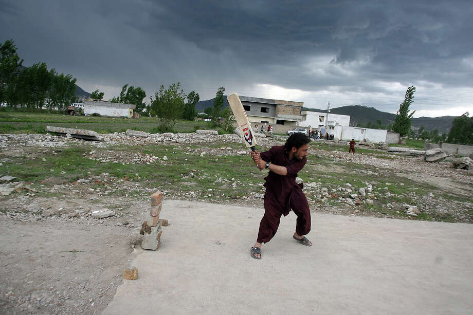 Local residents play cricket at the site of the demolished compound of slain Al-Qaeda leader Osama bin Laden in northern Abbottabad on May 1, 2012, ahead of bin Laden's first death anniversary. The al-Qaeda founder Osama bin Laden and 9/11 mastermind was killed on May 2, 2011 in a secret US Navy SEAL operation in a walled-off compound in the Pakistani garrison town of Abbottabad, north of the Pakistani capital. Photo: SAJJAD QAYYUM, AFP/Getty Images / 2012 AFP