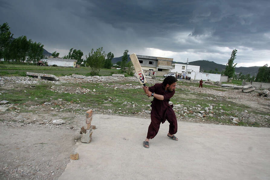Local residents play cricket at the site of the demolished compound of slain Al-Qaeda leader Osama b