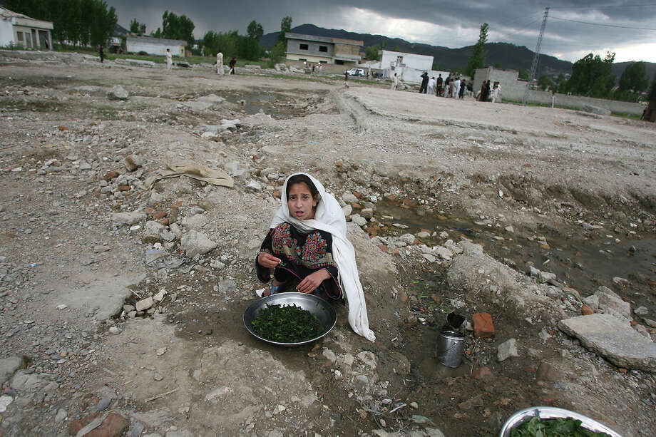 A Pakistani girl washes vegetables at the site of the demolished compound of slain Al-Qaeda leader Osama bin Laden in northern Abbottabad on May 1, 2012, ahead of bin Laden's first death anniversary. The al-Qaeda founder Osama bin Laden and 9/11 mastermind was killed on May 2, 2011 in a secret US Navy SEAL operation in a walled-off compound in the Pakistani garrison town of Abbottabad, north of the Pakistani capital. Photo: SAJJAD QAYYUM, AFP/Getty Images / 2012 AFP