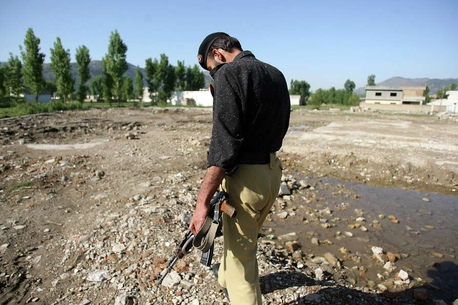 A Pakistani policeman walks at the site of the demolished compound of slain Al-Qaeda leader Osama bi