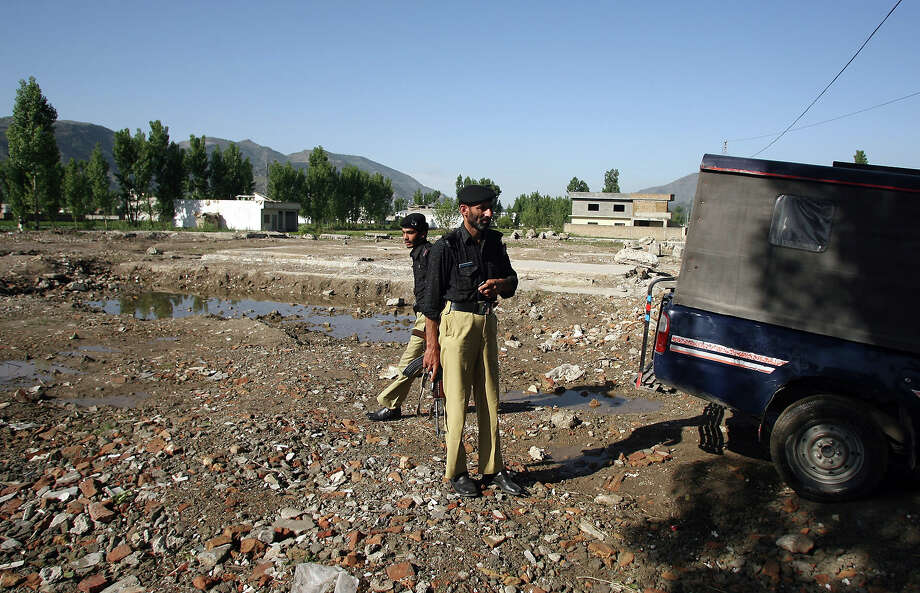 Pakistani policemen stand guard at the site of the demolished compound of slain Al-Qaeda leader Osama bin Laden in northern Abbottabad on May 2, 2012. Pakistan was in a state of high alert over fears terrorists could mark the first anniversary of bin Laden's killing by American Navy SEALs with revenge attacks. The al-Qaeda founder Osama bin Laden and 9/11 mastermind was killed on May 2, 2011 in a secret US Navy SEAL operation in a walled-off compound in the Pakistani garrison town of Abbottabad, north of the Pakistani capital. Photo: SAJJAD QAYYUM, AFP/Getty Images / 2012 AFP