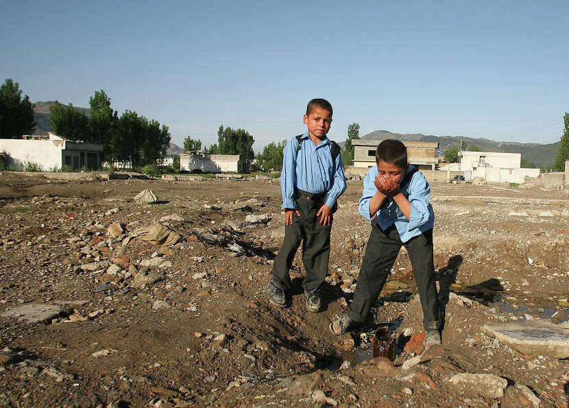 A Pakistani schoolboy drinks water at the site of the demolished compound of slain Al-Qaeda leader O