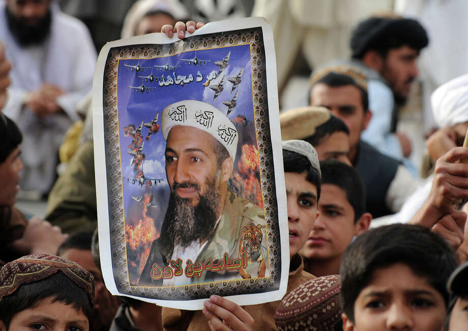 Supporters of hard line pro-Taliban party Jamiat Ulema-i-Islam-Nazaryati (JUI-N) carry portraits of the slain Al-Qaeda leader Osama bin Laden as they gather during an anti-US rally in Quetta on May 2, 2012 on the first anniversary of the death of Osama bin Laden. Pakistan was in a state of high alert on May 2, over fears militants will launch revenge attacks on the first anniversary of Osama bin Laden's killing by American Navy SEALs. The al-Qaeda founder Osama bin Laden and 9/11 mastermind was killed on May 2, 2011 in a secret US Navy SEAL operation in a walled-off compound in the Pakistani garrison town of Abbottabad, north of the Pakistani capital. Photo: BANARAS KHAN, AFP/Getty Images / 2012 AFP