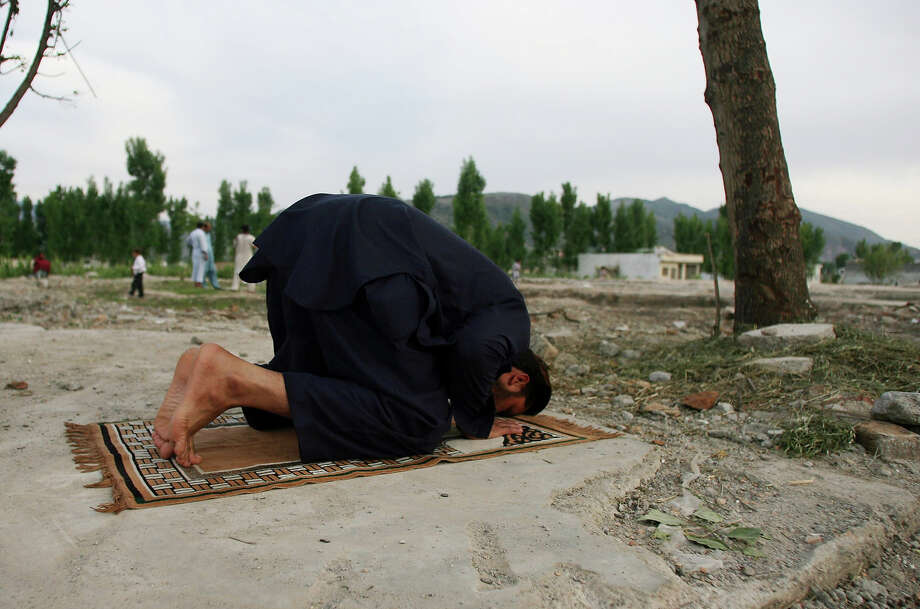 A Pakistani man prays near the site of the demolished compound of slain Al-Qaeda leader Osama bin Laden in Abbottabad, on May 2, 2012, on the anniversary of the death of Osama bin Laden. Pakistan was in a state of high alert over fears terrorists could mark the first anniversary of bin Laden's killing by American Navy SEALs with revenge attacks. The al-Qaeda founder Osama bin Laden and 9/11 mastermind was killed on May 2, 2011 in a secret US Navy SEAL operation in a walled-off compound in the Pakistani garrison town of Abbottabad, north of the Pakistani capital. Photo: SAJJAD QAYYUM, AFP/Getty Images / 2012 AFP