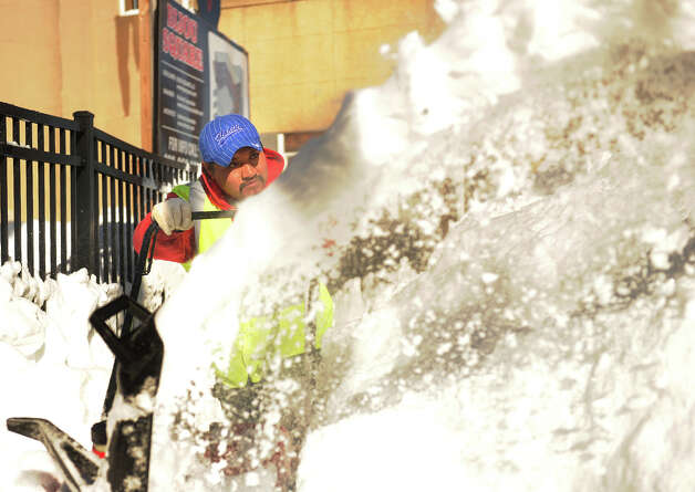Roberto Cuaya uses a snow blower to clear sidewalks in the Bijou Square development of Fairfield Avenue in Bridgeport, Conn. on Sunday, February 10, 2013. Photo: Brian A. Pounds / Connecticut Post