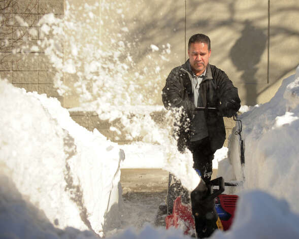 Mike Marrero of Bridgeport uses a snow blower to clear sidewalks in front of the Holiday Inn on Main Street in downtown Bridgeport, Conn. on Sunday, February 10, 2013. Photo: Brian A. Pounds / Connecticut Post