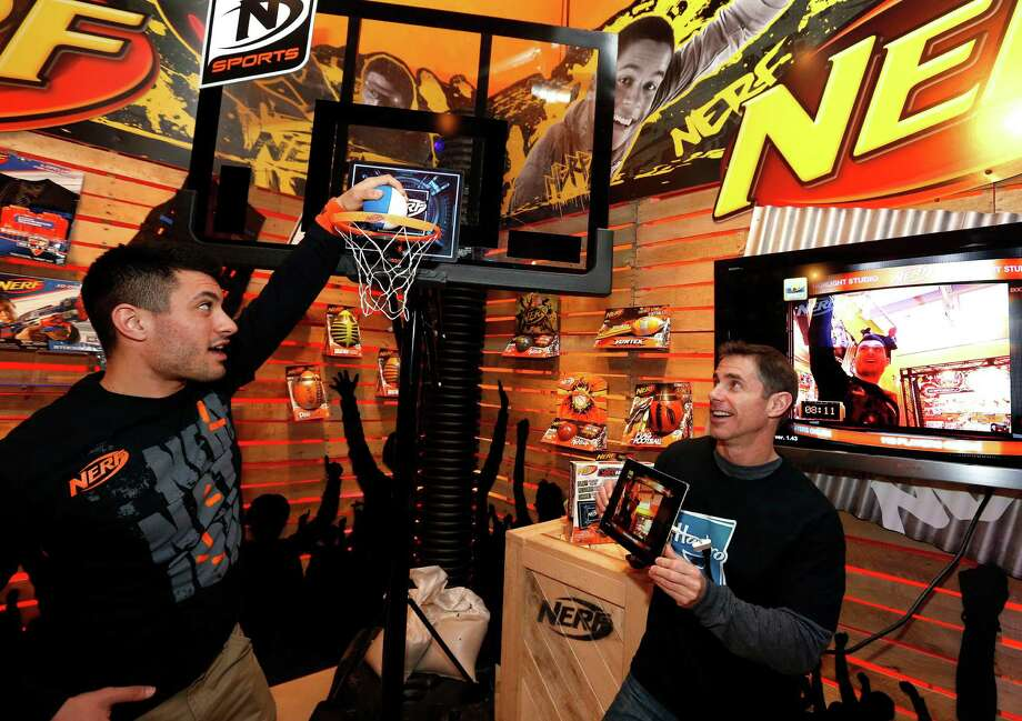 Demonstrators L.J. Regine, left, and Brian McMullan records their shots while playing with the NERF N-SPORTS CYBERHOOP set in Hasbro's showroom at the American International Toy Fair, Saturday, Feb. 9, 2013, in New York.  The CYBERHOOP set works with a free app to track game stats, capture games on video, and provide commentary. The CYBERHOOP app also allows players to play virtually and share highlights with friends online. (Photo by Jason DeCrow/Invision for Hasbro/AP Images) Photo: Jason DeCrow, Associated Press / Invision
