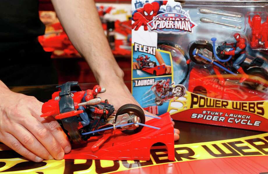 Toy demonstrator Clayton Hodges pulls back on the ULTIMATE SPIDER-MAN POWER WEBS STUNT LAUNCH SPIDER CYCLE, of Hasbro's line of toys based on the Ultimate Spider-Man TV show, and prepares to launch it off a ramp in the company's showroom at the American International Toy Fair, Saturday, Feb. 9, 2013, in New York. (Photo by Jason DeCrow/Invision for Hasbro/AP Images) Photo: Jason DeCrow, Associated Press / Invision