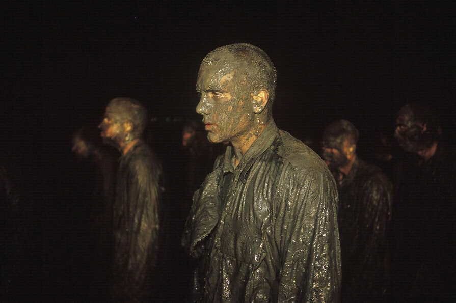 Navy Seal trainees stand at attention after crawling through mud and being subjected to frigid Pacif