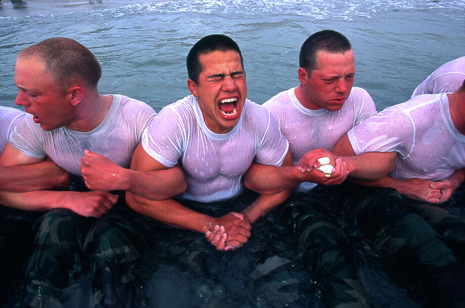 Navy Seal trainees lock arms upon entering the frigid Pacific waters in this undated photo taken in 2000 at the Coronado Naval Amphibious Base in San Diego, California. Photo: Joe McNally, Getty Images / 2000 Joe McNally