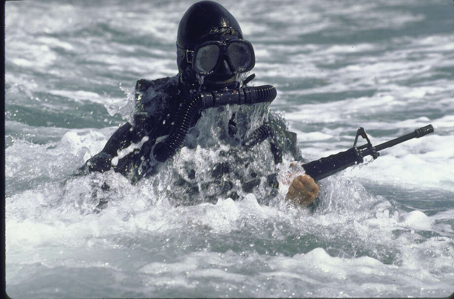 Excellent shot of gun-toting US Navy Seal in full diving gear emerging from surf. Photo: Mark Meyer, Time & Life Pictures/Getty Image / Mark Meyer
