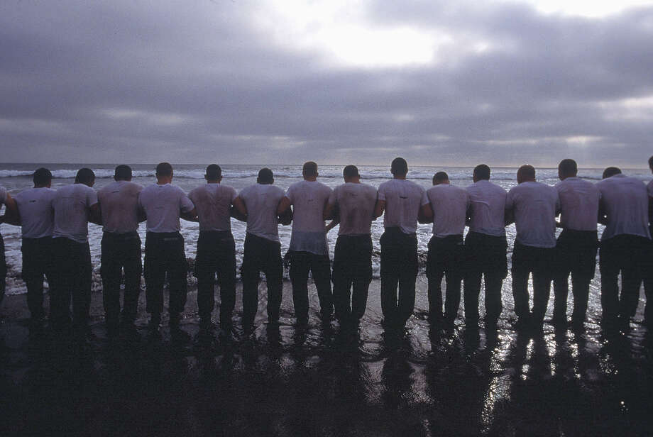 A line of Navy Seal trainees lock arms before re-entering the frigid Pacific surf in this undated photo taken in 2000 at the Coronado Naval Amphibious Base in San Diego, California. Photo: Joe McNally, Getty Images / 2000 Joe McNally