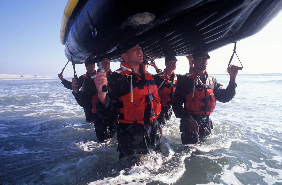 A group of Navy Seal trainees struggle under the weight of a heavy inflatable boat in this undated photo taken in 2000 at the Coronado Naval Amphibious Base in San Diego, California. Photo: Joe McNally, Getty Images / 2000 Joe McNally