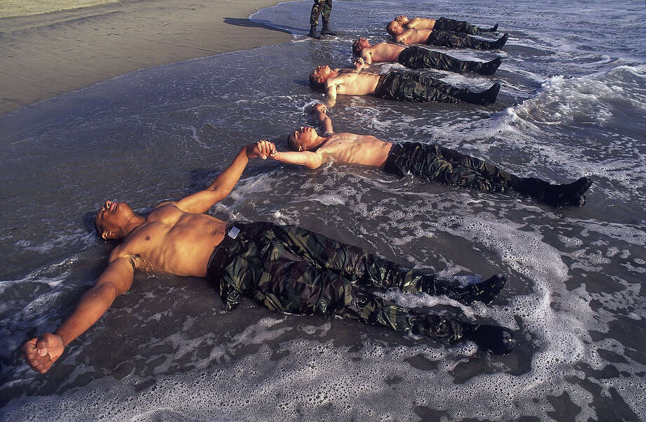 Navy Seal trainees lie in the frigid Pacific surf in this undated photo taken in 2000 at the Coronado Naval Amphibious Base in San Diego, California. Photo: Joe McNally, Getty Images / 2000 Joe McNally
