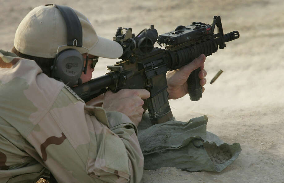 A U.S. Navy SEAL fires his M-4 assault rifle during a training session with Iraqi army scouts July 2