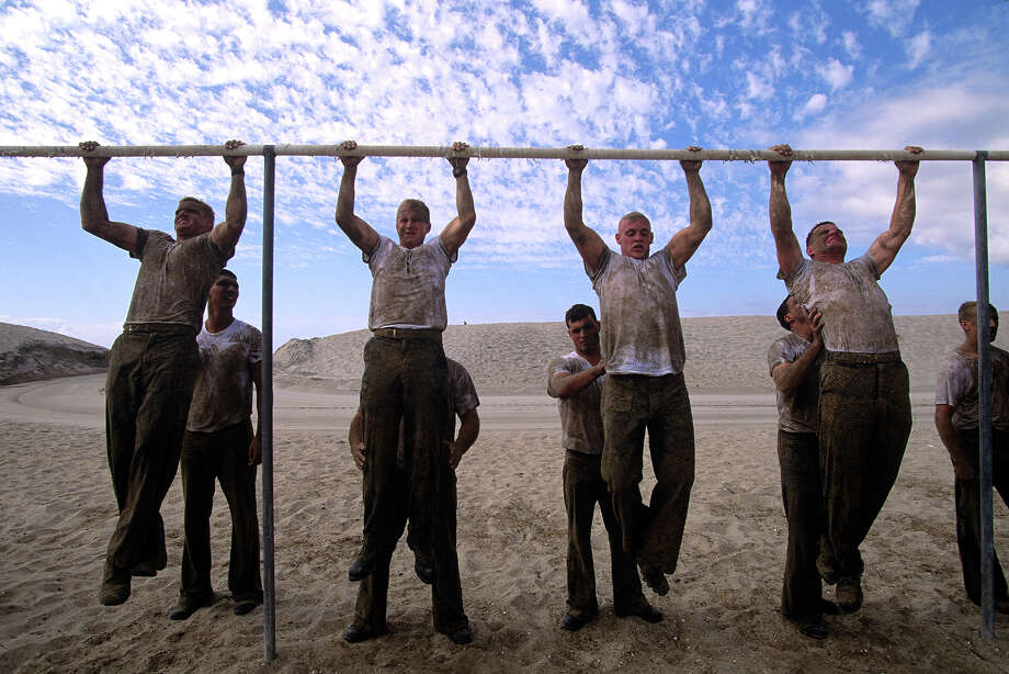 Fatigued Navy Seals struggle to do pull ups in August of 2005 on the beach at Hell Week training in Coronado, California. Photo: Joe McNally, Getty Images / 2005 Joe McNally
