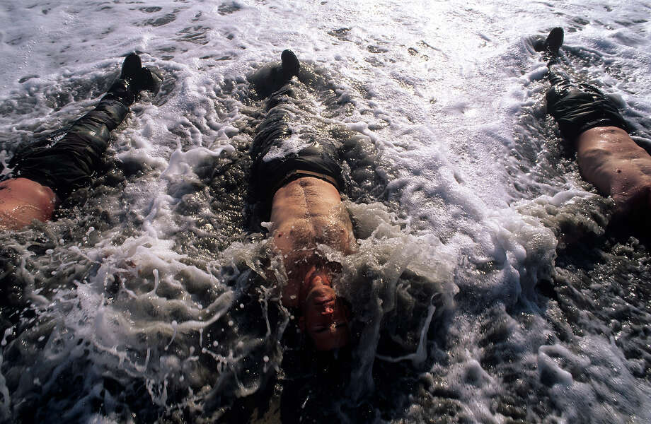 Navy Seal trainees are forced to lie in the frigid surf in August of 2005 during Hell Week at a beach in Coronado, California. Photo: Joe McNally, Getty Images / 2005 Joe McNally