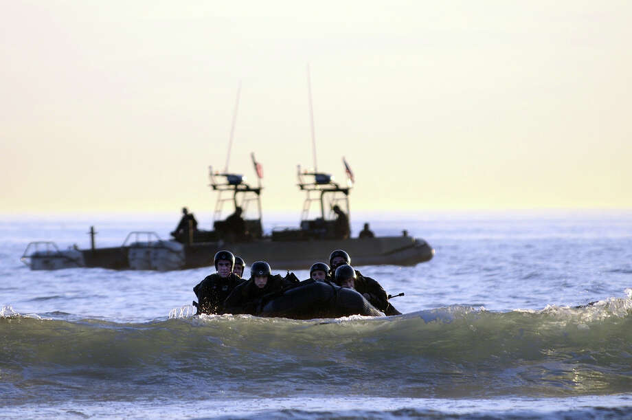 Students in Sea Air and Land (SEAL) qualification training navigate the surf off the cost of Coronado during a maritime operations training exercise October 28, 2010 in Coronado, California. The 26-week program takes students from a very basic level, to a more advanced degree of technical and tactical operations. Photo: U.S. Navy, Getty Images / 2010 US Navy