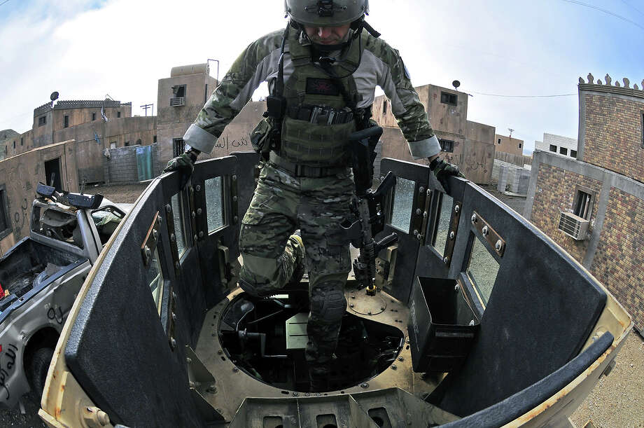 A Navy special warfare specialist (SEAL) assigned to Seal Team 17, a unit composed of both active and reserve component members based in Coronado, Calif., climbs into the turret gunner position during a mobility training exercise through a simulated city December 10, 2010 in San Clememnte Island, California. Photo: U.S. Navy, Getty Images / 2010 US Navy