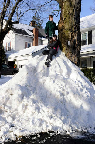 "Haylee Hughes, 12, sitting, and Bryce Benson, 10, watch for cars to pass by the ""mountain"" of snow that Bryce and his father Chris, created against a tree at the family's home on Abbott Avenue in Danbury, Conn. Feb. 10, 2013. A blizzard dumped almost two feet of snow on the Danbury area all day friday and early Saturday morning. Photo: Carol Kaliff / The News-Times"
