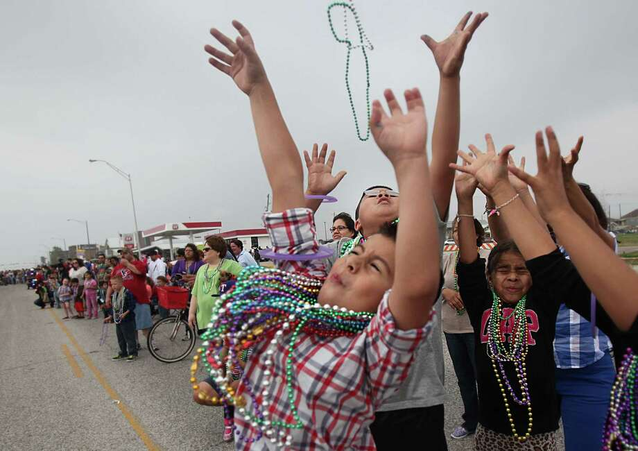 Daniel Loredo and Damian Ruiz attempt to catch beads during the  Krewe of Barkus & Meoux Parade along the Seawall on Sunday, Feb. 10, 2013, in Galveston. Photo: Mayra Beltran, Houston Chronicle / © 2013 Houston Chronicle