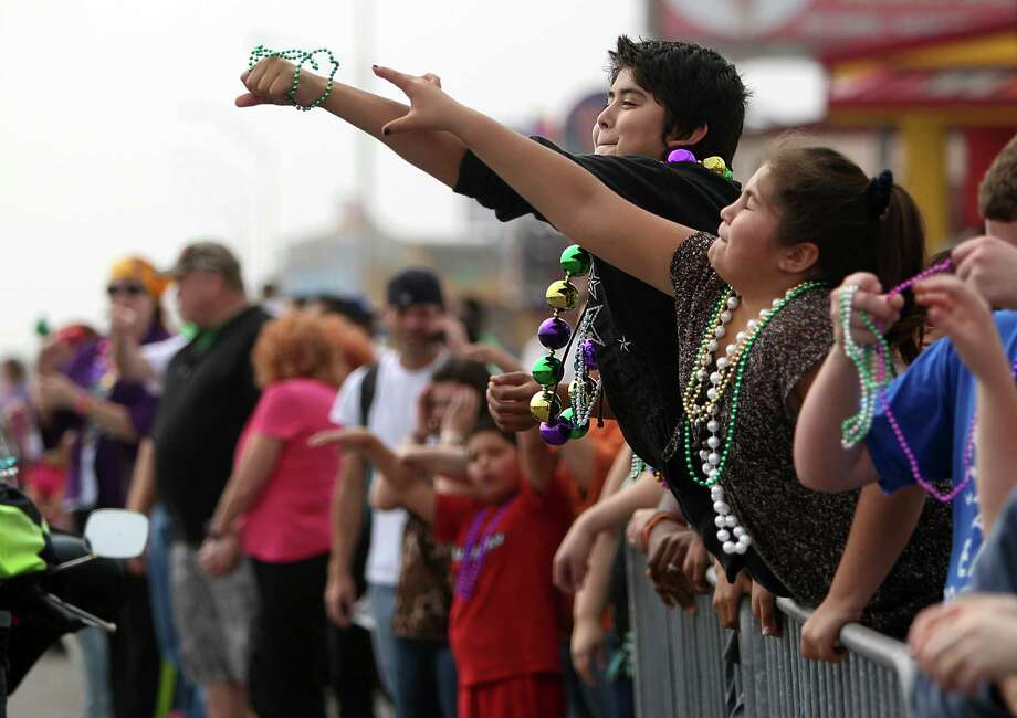 Parade spectators reach out for beads during the Krewe of Barkus & Meoux Parade along the Seawall on Sunday, Feb. 10, 2013, in Galveston. Photo: Mayra Beltran, Houston Chronicle / © 2013 Houston Chronicle