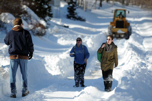 Pedestrians walk in the wake of a tractor as it make the first trip to clear snow from the north section of Cutspring Rd., in Stratford, Conn., Feb. 10th, 2013. Photo: Ned Gerard