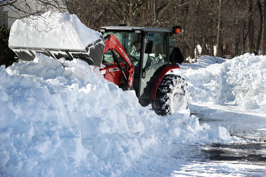 Tom Dugas uses a tractor to help remove snow from a neighbor's driveway in Stratford, Conn., Feb. 10th, 2013. Photo: Ned Gerard / Connecticut Post