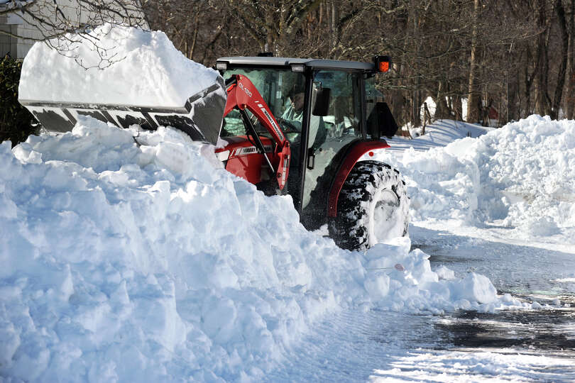 Tom Dugas uses a tractor to help remove snow from a neighbor's driveway in Stratford, Conn., Feb. 10