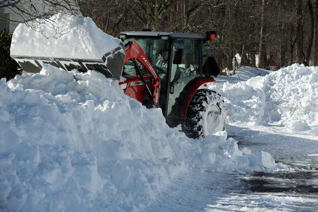 Tom Dugas uses a tractor to help remove snow from a neighbor's driveway in Stratford, Conn., Feb. 10th, 2013. Photo: Ned Gerard