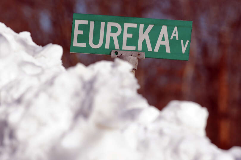 Plowed snow stands as high as the street sign on Eureka Ave., in Stratford, Conn., Feb. 10th, 2013.