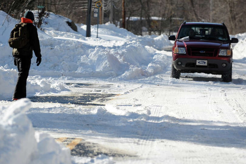 A pedestrian uses caution as he walks along Hawley Lane, in Stratford, Conn., Feb. 10th, 2013.