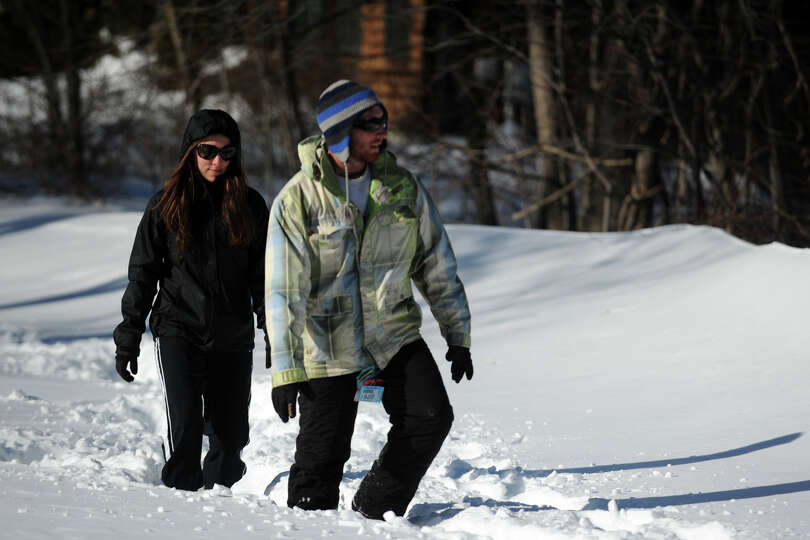 Michael Patria and Jessica Tumio walk in the snow on an unplowed section of Cutspring Rd., in Stratf