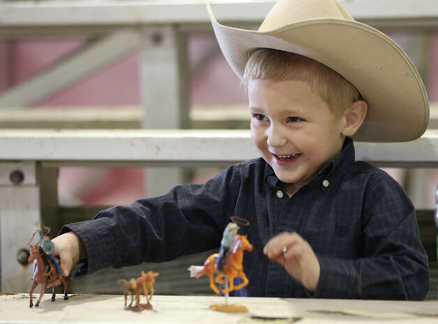 Colton Ranly, 3, of Lott, Texas plays with his toy cowboys during the San Antonio Stock Show and Rodeo, Sunday, Feb. 10, 2013. Lott was sitting with his mother while his dad a veterinarian student, worked the Open Breeding Beef Cattle division. Photo: Jerry Lara, San Antonio Express-News / ©2013 San Antonio Express-News