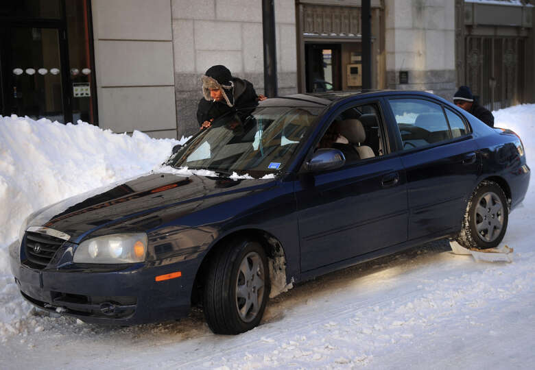 A man pushes out a stranded motorist on Main Street in downtown Bridgeport, Conn. on Sunday, Februar