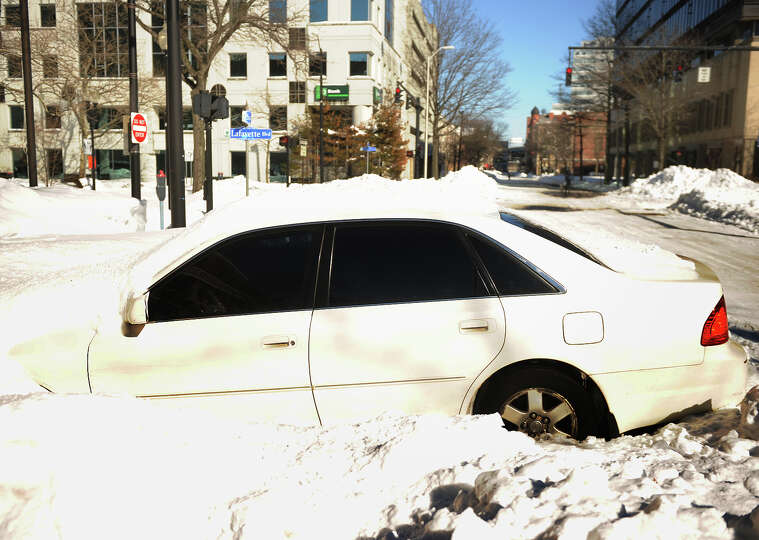 An abandoned car is buried in the snow on State Street in downtown Bridgeport, Conn. on Sunday, Febr