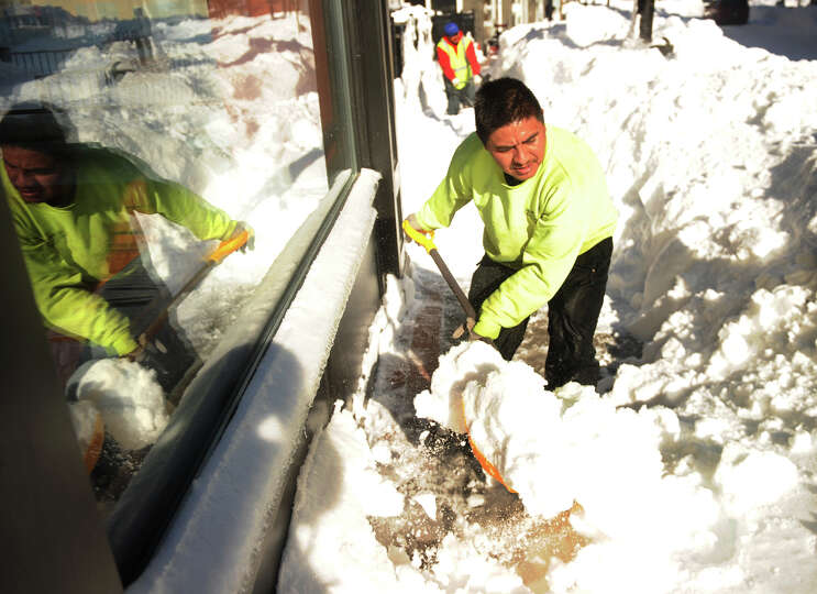 Arturo Sanchez of Bridgeport shovels sidewalks in the Bijou Square development of Fairfield Avenue i