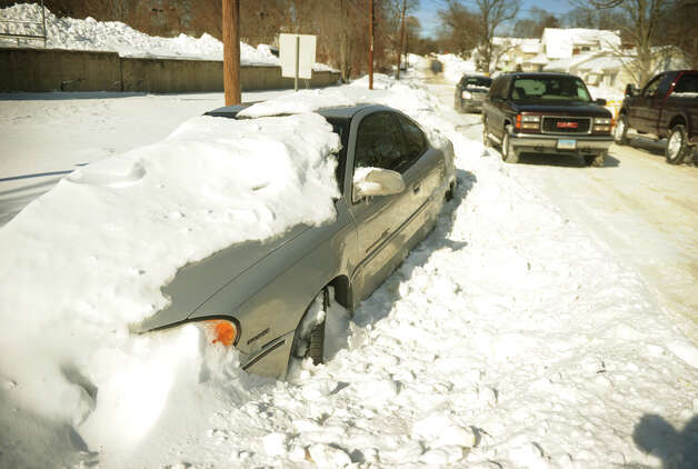An abandoned car is buried in the snow on High Street in Milford, Conn. on Sunday, February 10, 2013. Photo: Brian A. Pounds / Connecticut Post
