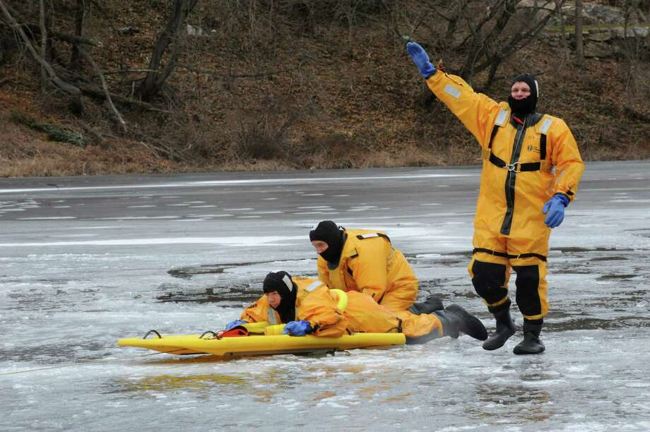 "Greenwich firefighter Whitney Welch,"" rescued,"" by firefighters Jimmy Stashenko, and Glen Krizan   conducing cold water rescue training on the Mianus River in Cos Cob, Thursday, Feb.7, 2013. Photo: Helen Neafsey / Greenwich Time"