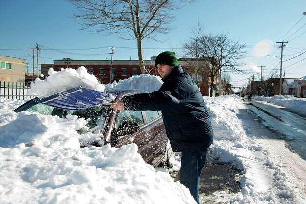 Edgar Chaves of Bridgeport works to free his late model Nissan Altima from the snow on the 1000 block of East Main St. in Bridgeport, Conn.on Sunday Feb. 10, 2013. Many residents are still digging out from the weekend blizzard. Photo: Mike Ross / Connecticut Post freelance