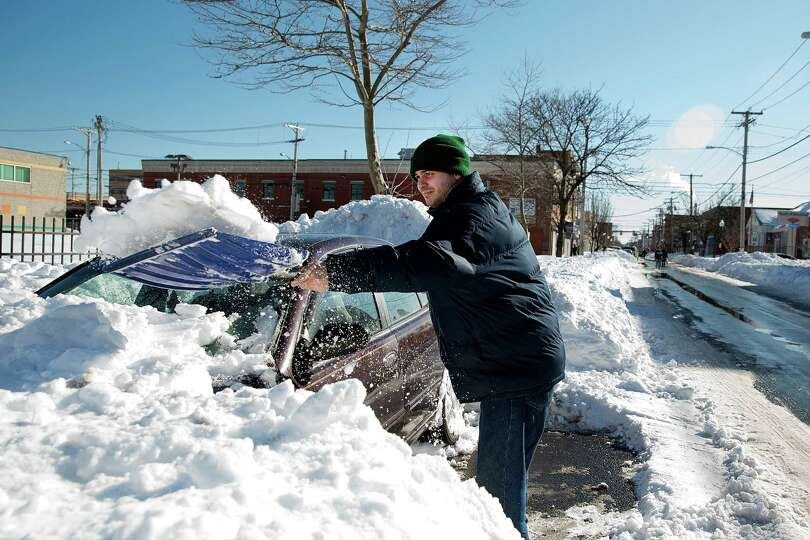 Edgar Chaves of Bridgeport works to free his late model Nissan Altima from the snow on the 1000 bloc