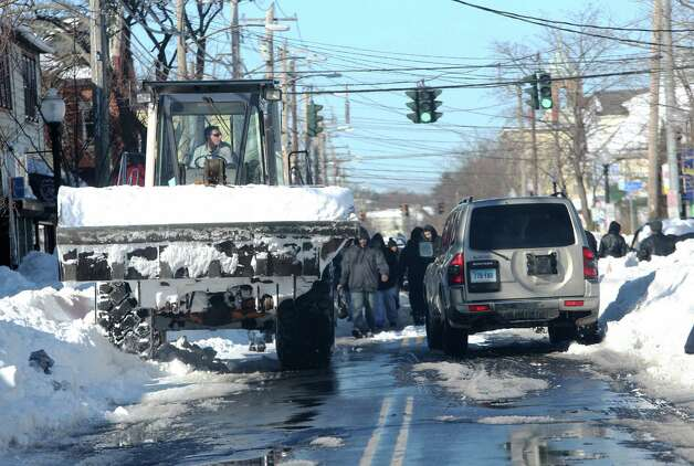 A large payloader makes it way down East Main Street in Bridgeport, Conn. to continue snow removal on  Sunday Feb. 10, 2013. Town officials and residents are still working to get out from under the weekend blizzard. Photo: Mike Ross / Connecticut Post freelance