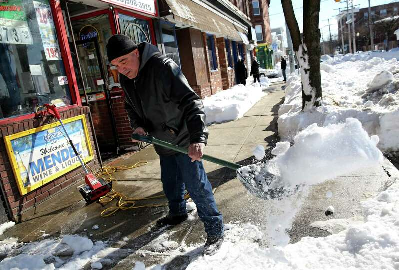 Jose Carrasquillo shovels snow in front of Mendez Wine & Liquor on East Main St. in Bridgeport, Conn
