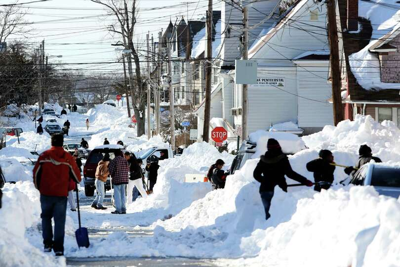 East Side residents on Putnam Ave. and East Main St. in Bridgeport, Conn. work to free their automob