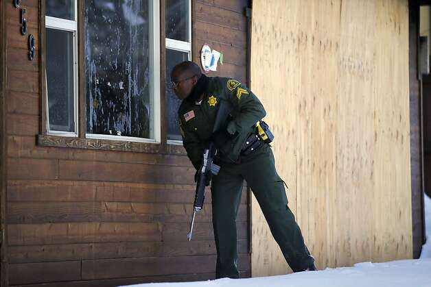 San Bernardino County Sheriff's Deputy Ken Owens checks a home in Big Bear Lake as police continue the search for Dorner across the region. Photo: Jae C. Hong, Associated Press